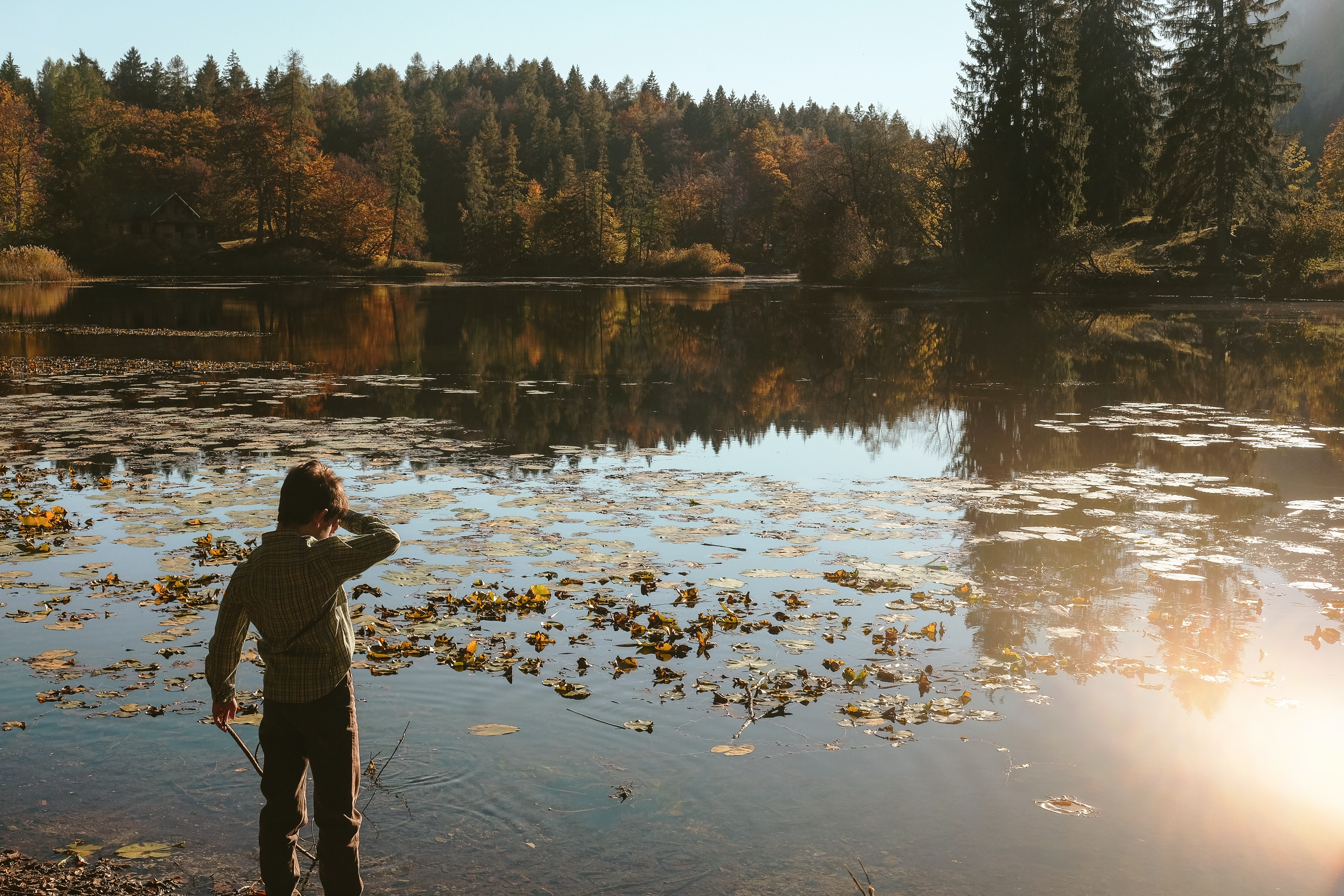 boy standing beside body of water during daytime