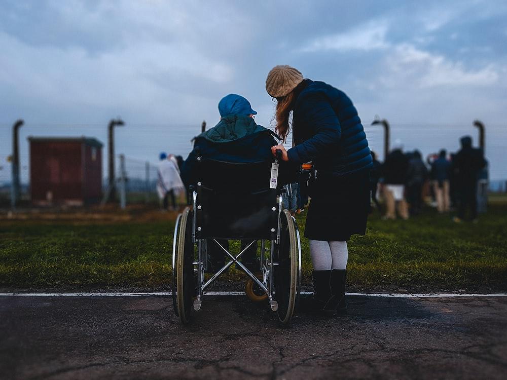 woman standing near person in wheelchair near green grass field