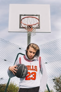 man wearing white and red Chicago Bulls Michael Jordan 23 jersey top and gray pullover hoodie while holding black basketball standing in front of white basketball system at daytime