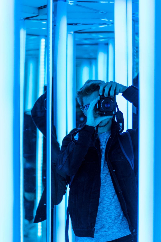 man taking photo in mirror using DSLR camera