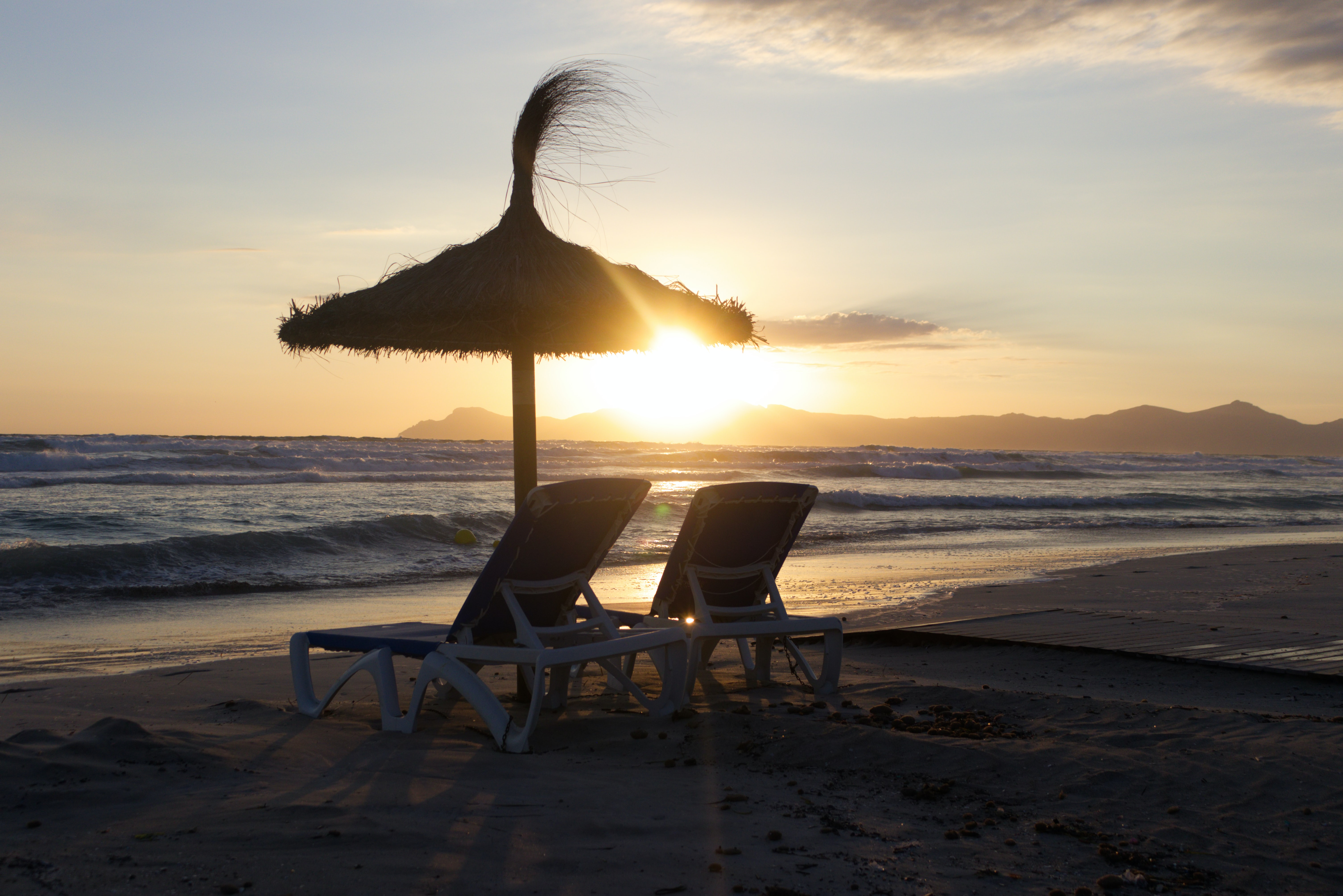 two brown chairs and umbrella on shore during golden hour