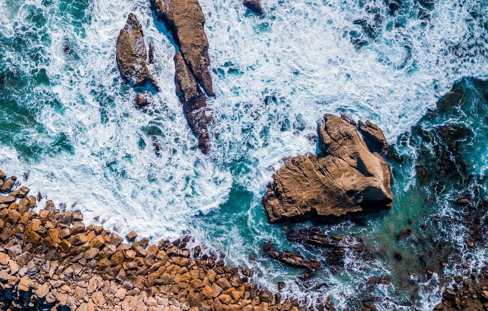 bird's eye view photography of seawaves splashing on rock during daytime