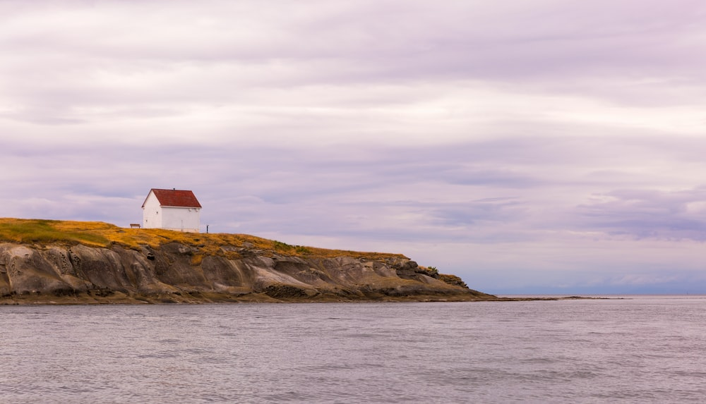 white and red wooden house near sea during daytime