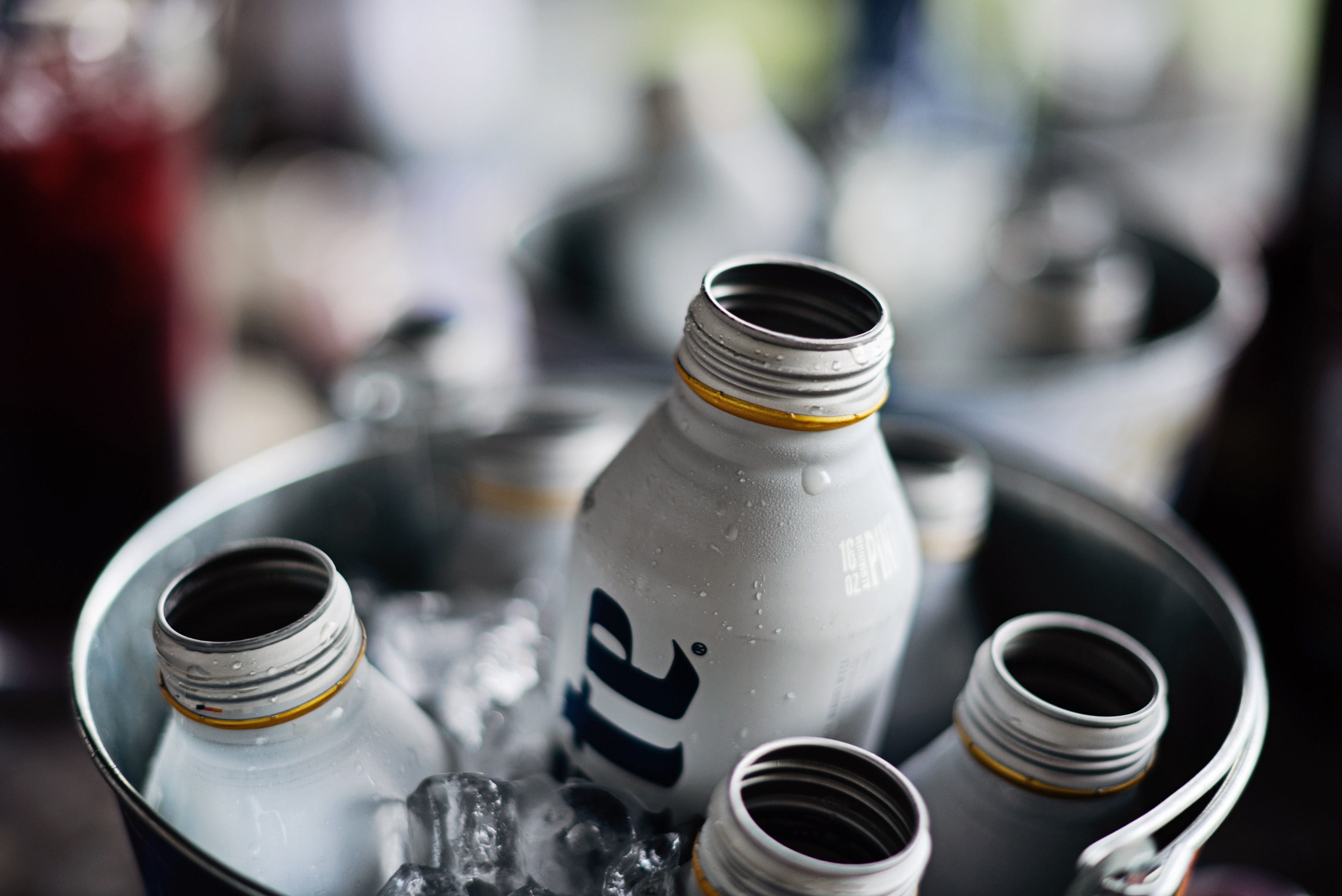 shallow focus photography of liquor bottles inside a bucket filled with ice