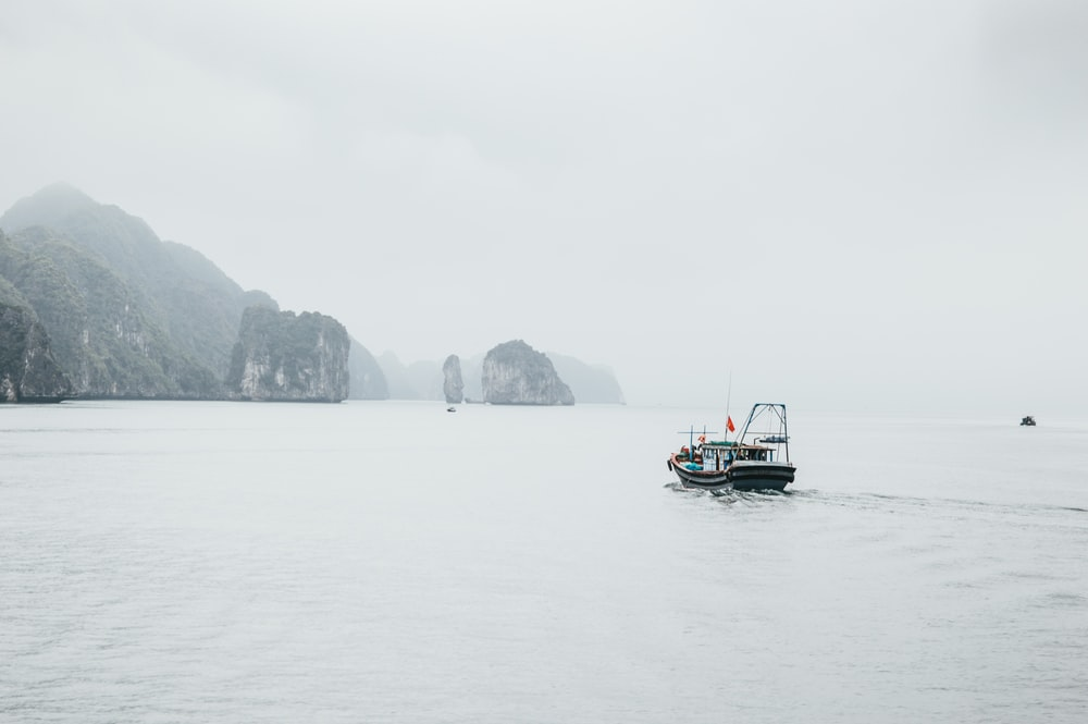 black and white boat near rock formation
