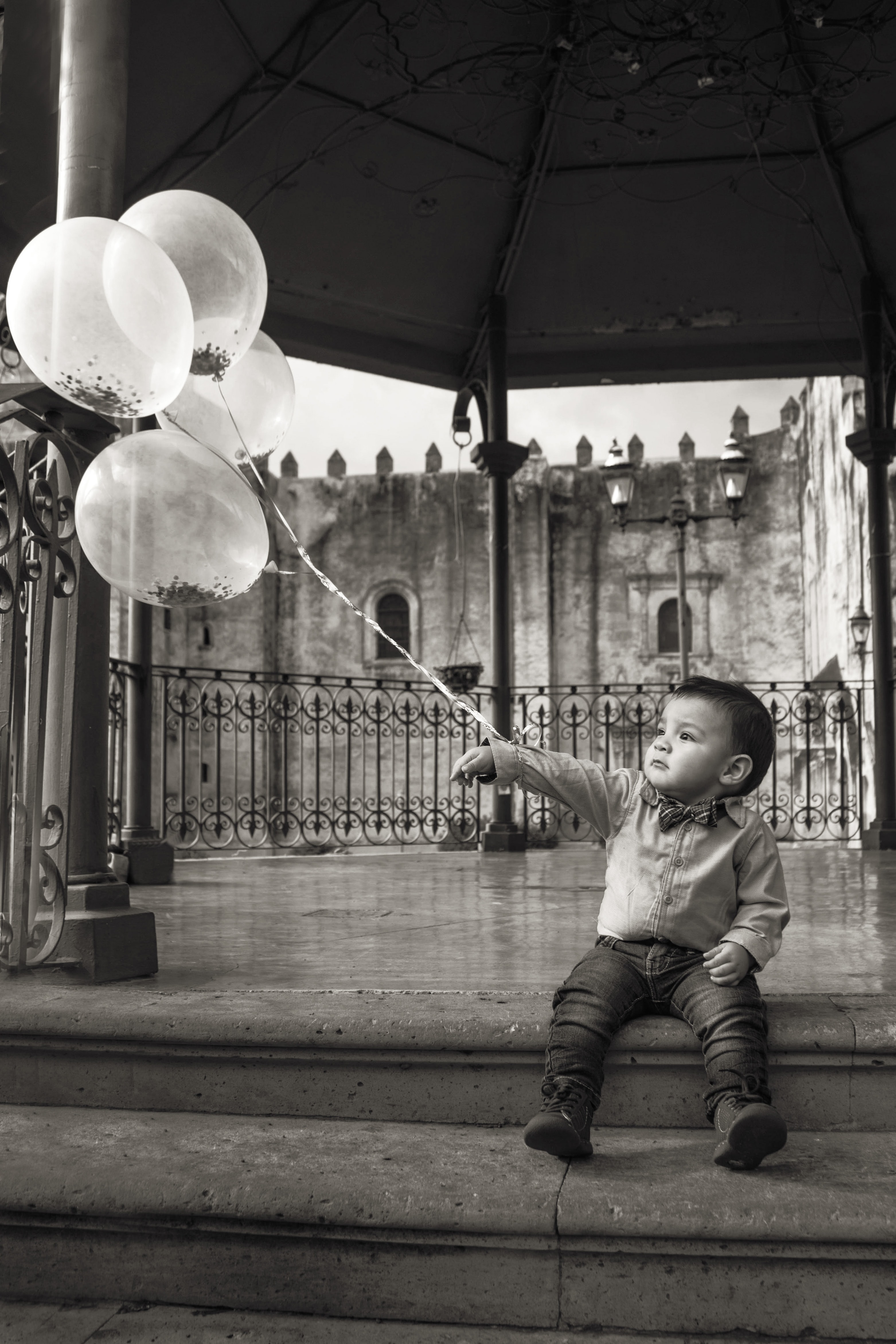 grayscale photography of boy holding balloons
