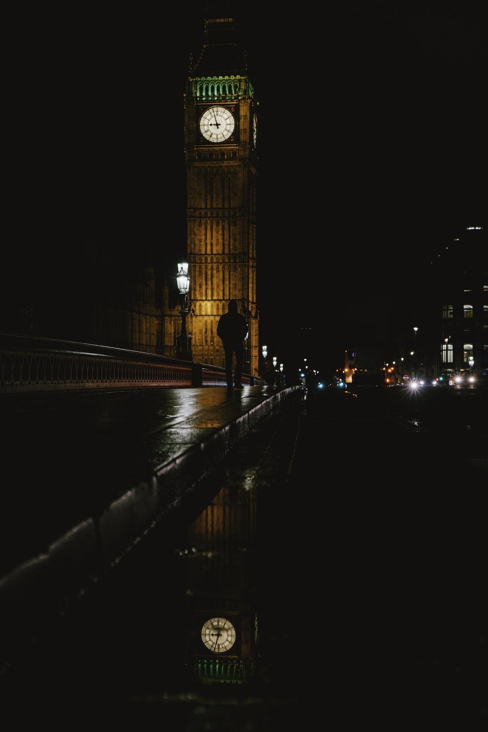 silhouette photo of man walking near Big Ben during nighttime