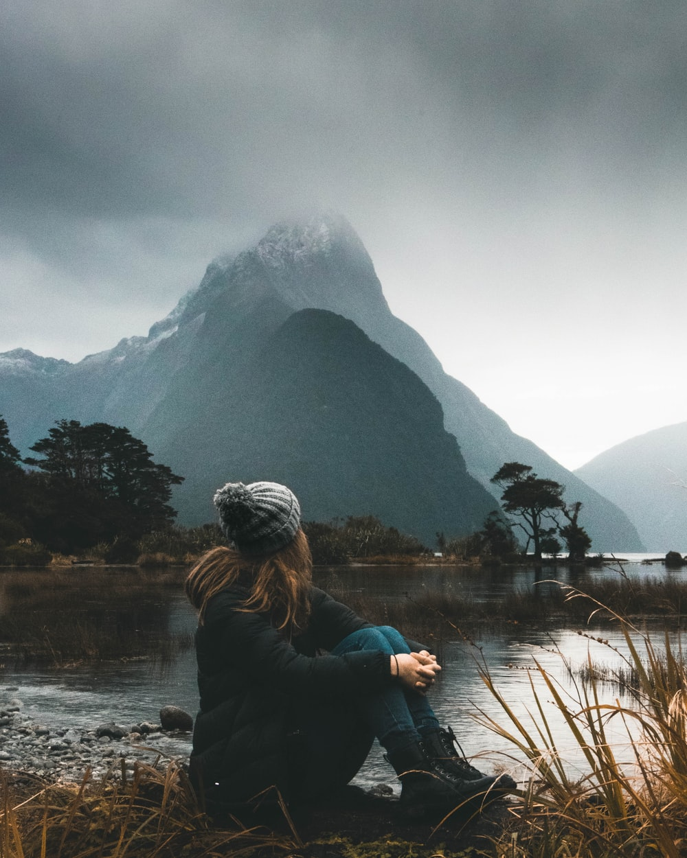 woman sitting near body of water looking at clouds