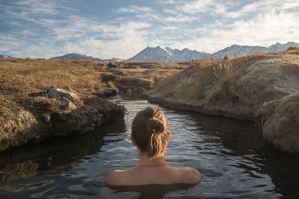 woman immerged in body of water between lands under cloudy sky