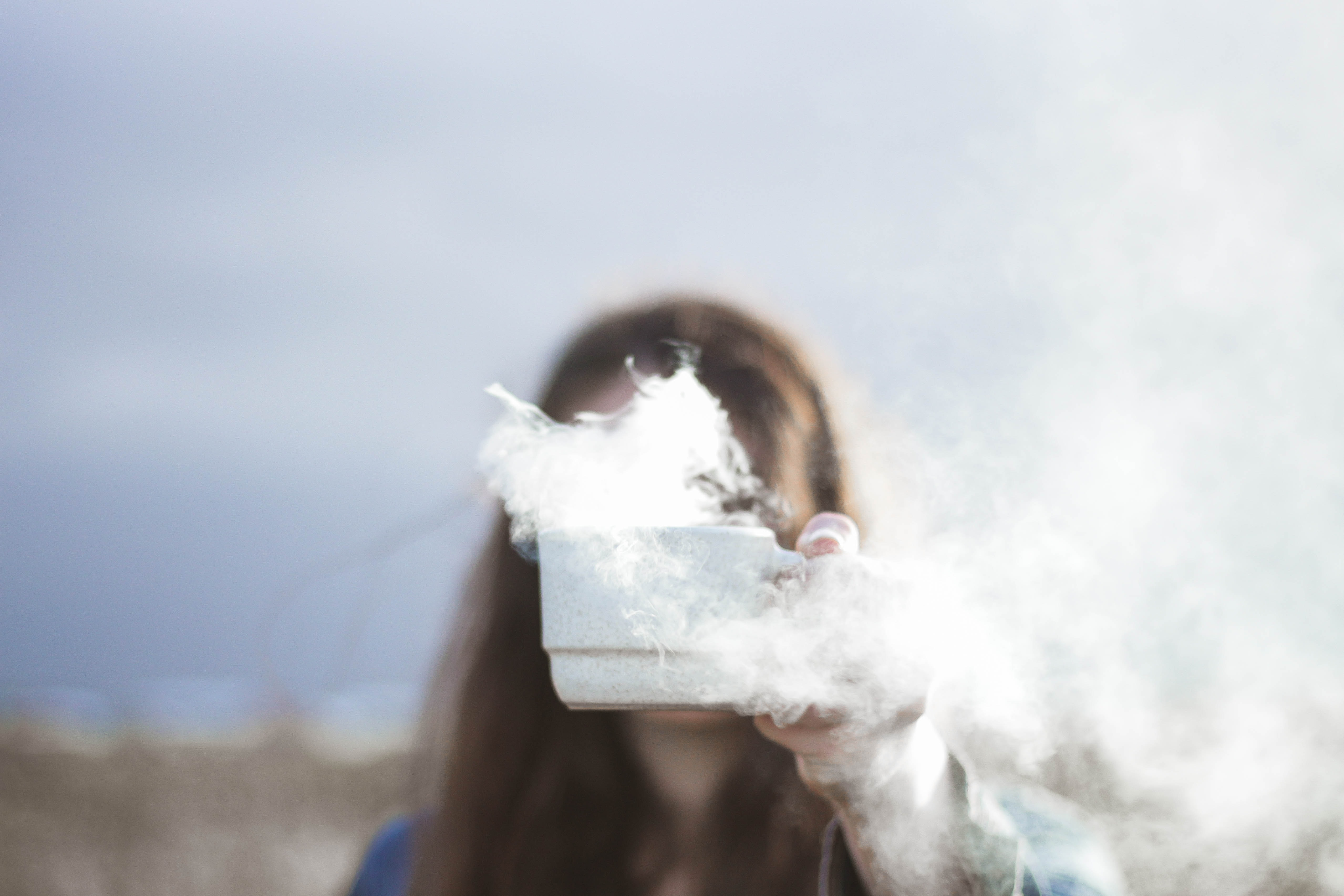 person holding white ceramic cup with smoke flowing inside