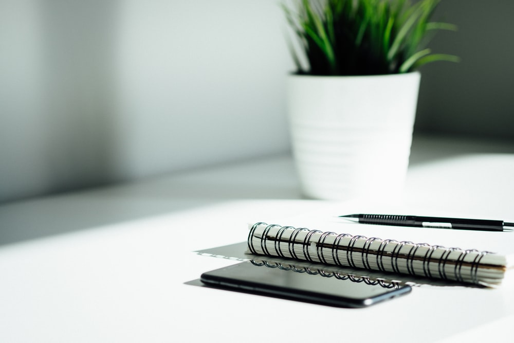 pen, notebook, and smartphone on table