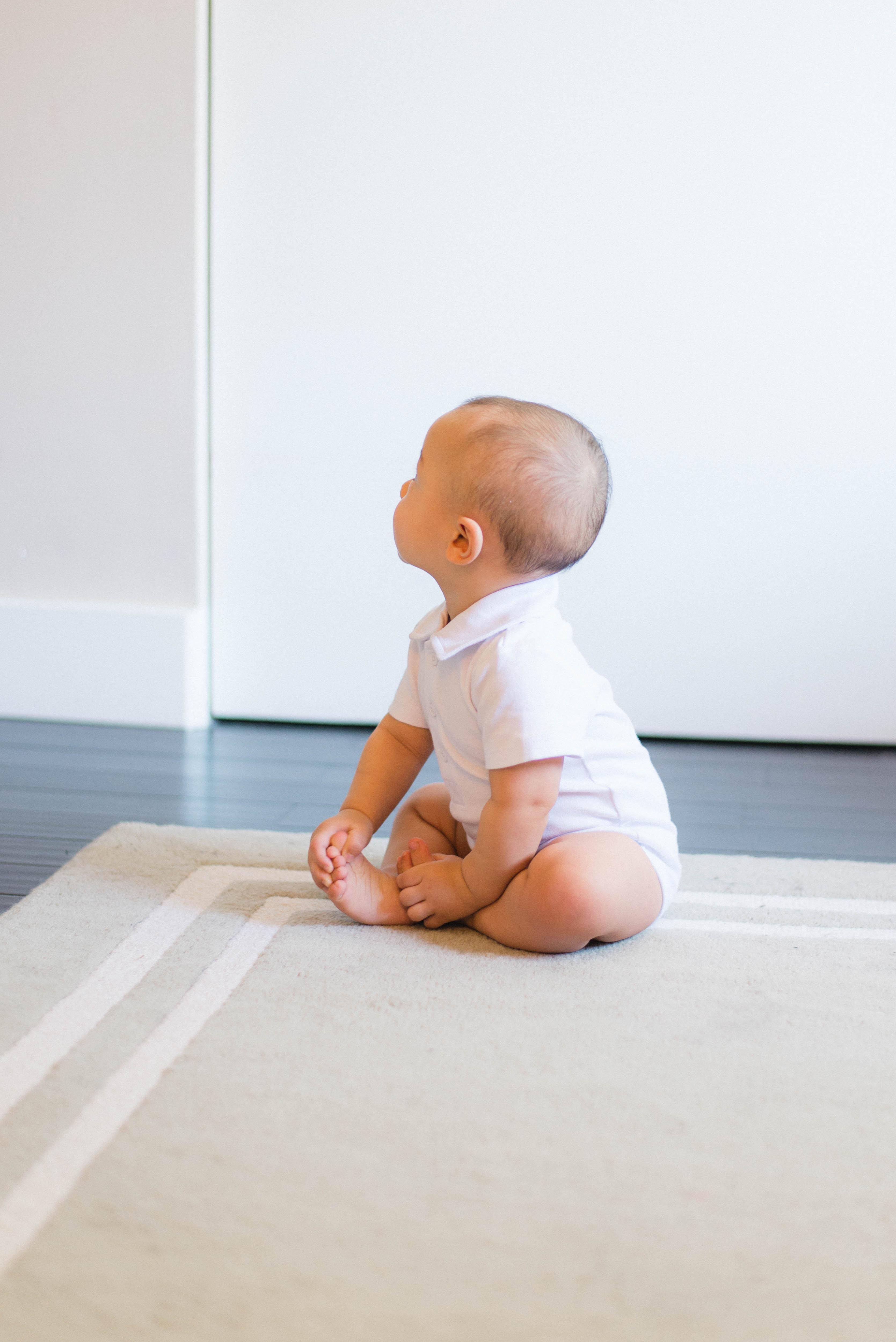 baby sitting on beige rug