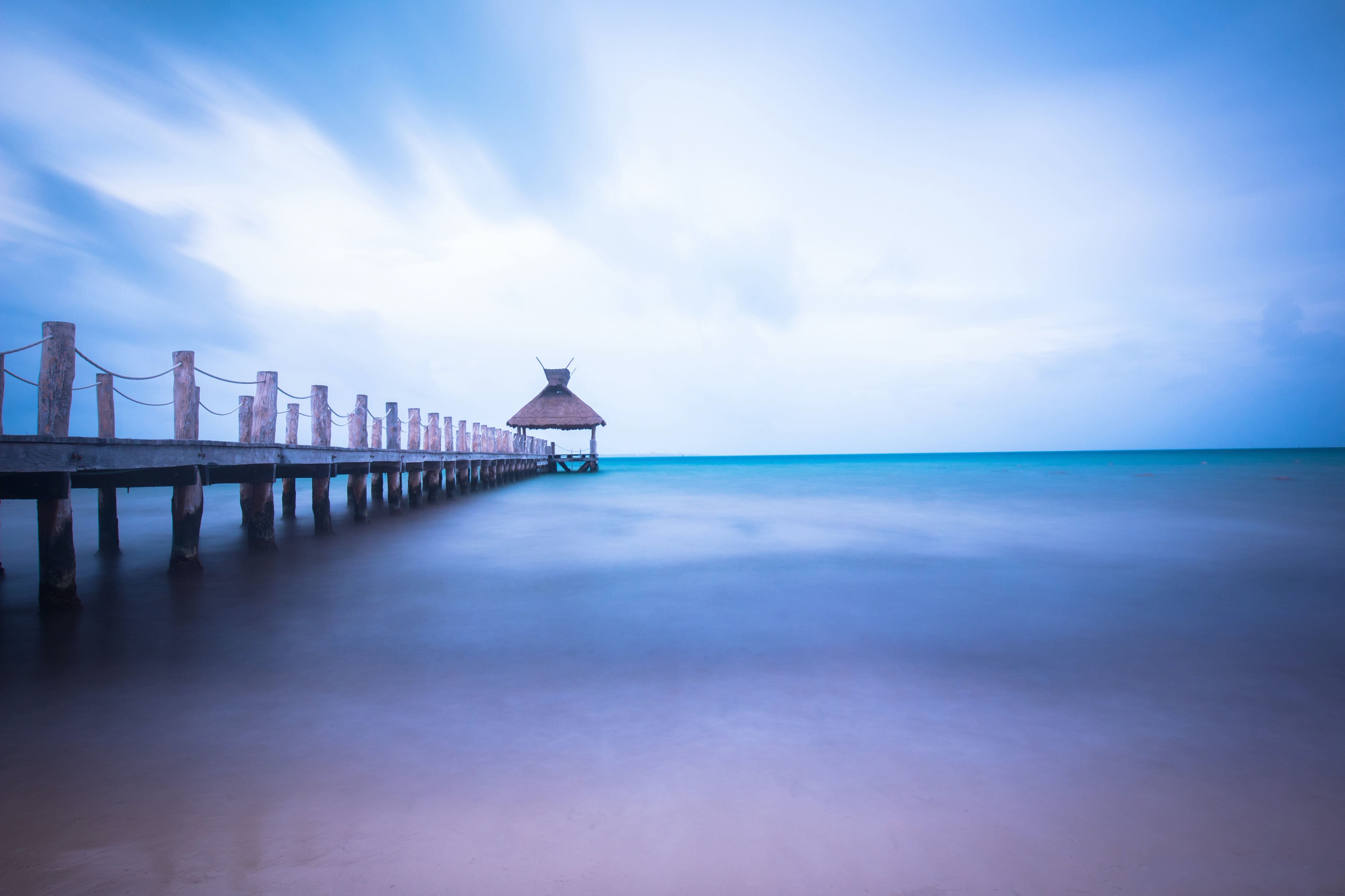 dock on body of water under cloudy sky