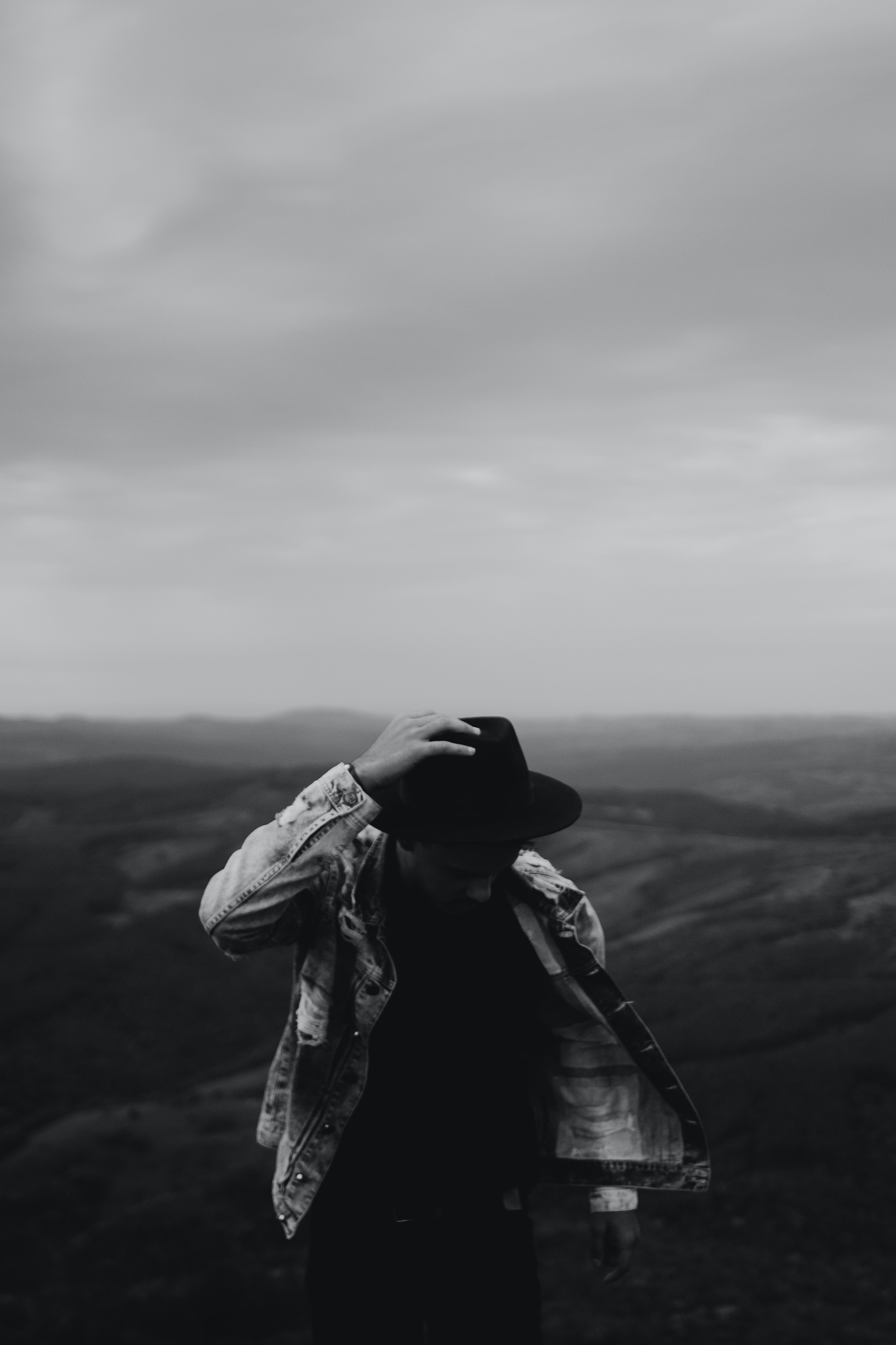 grayscale photography of man holding his hat