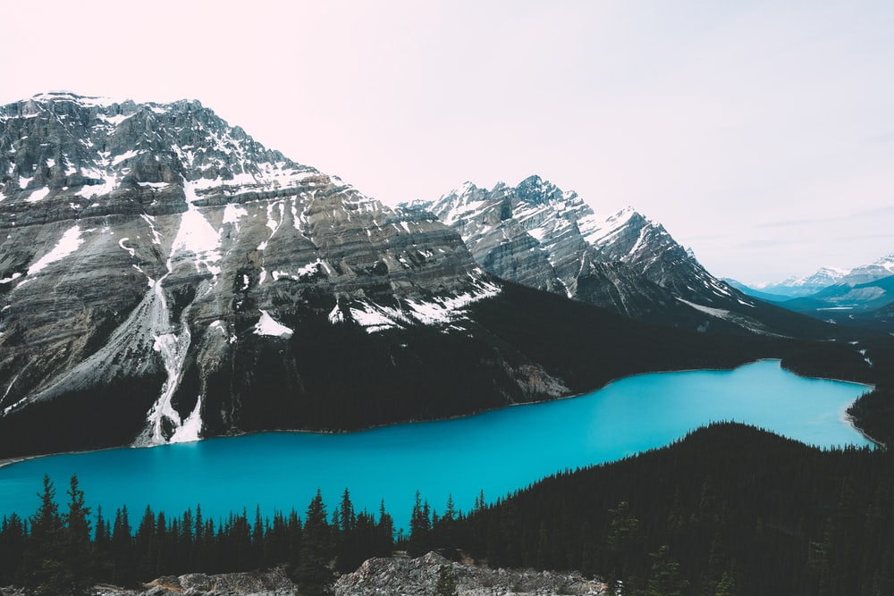 body of water across mountain during daytime