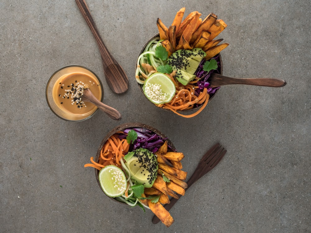 salad on brown wooden bowl with dip