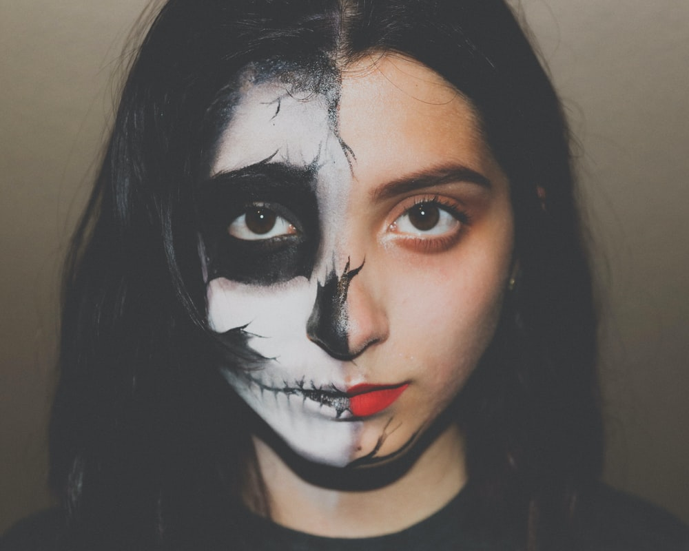 woman with skull paint on her half face
