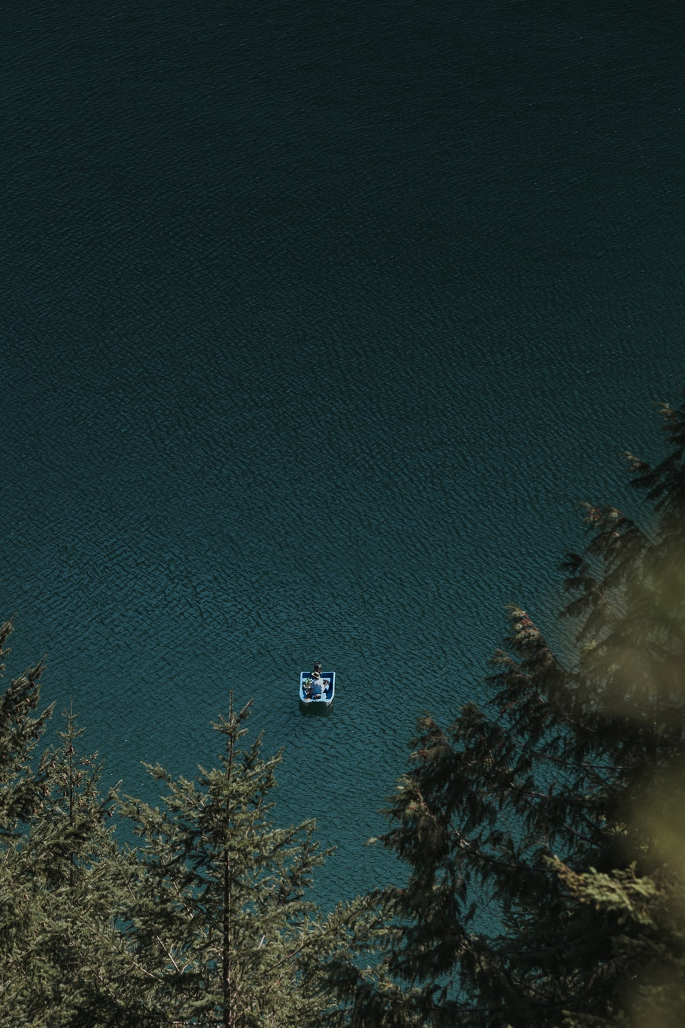 bird's eye view of person on boat on calm body of water