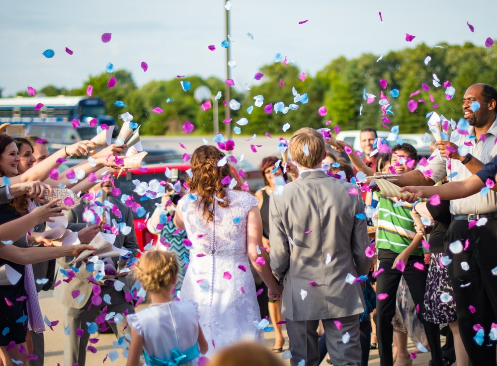newly wed couple surrounded by people throwing confetti