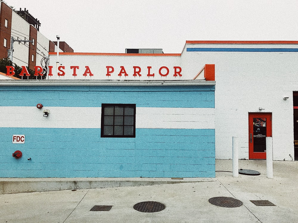 white and blue painted concrete building with Barista Parlor sign