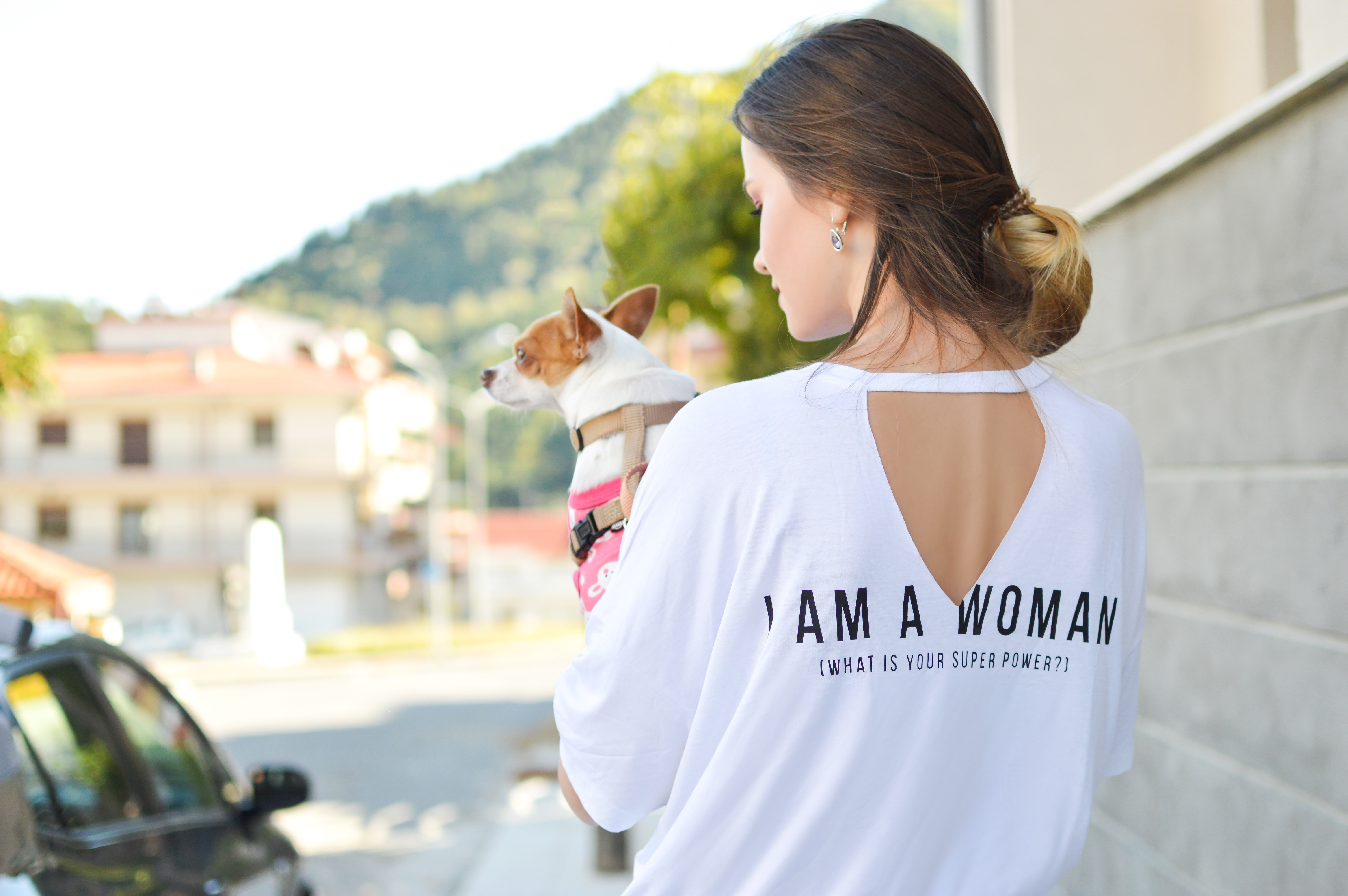 woman wearing white elbow-sleeved shirt while holding dog near concrete building during daytime