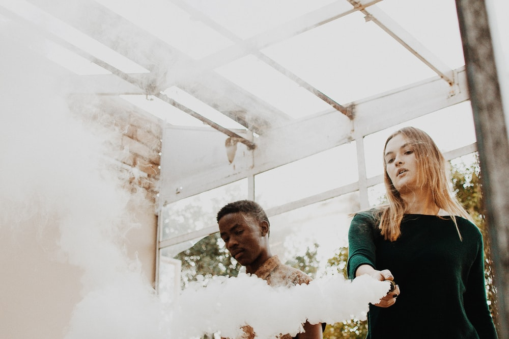 woman holding device emitting smoke beside man