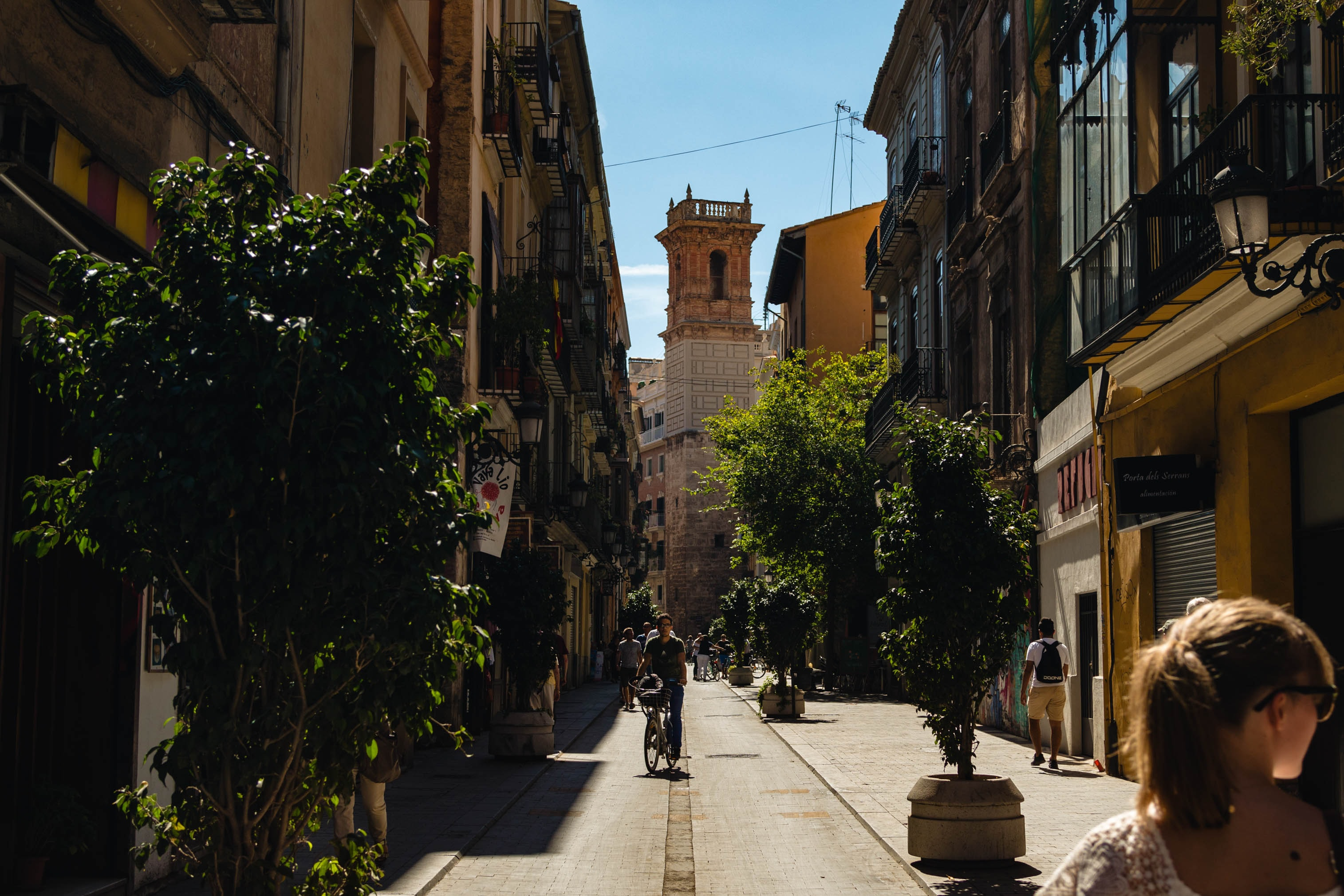 man riding bicycle near narrow street surrounded by buildings during daytime