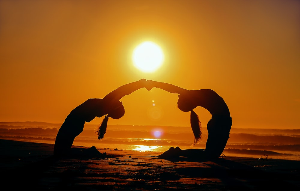 silhouette of two woman bending while holding hands during sunset