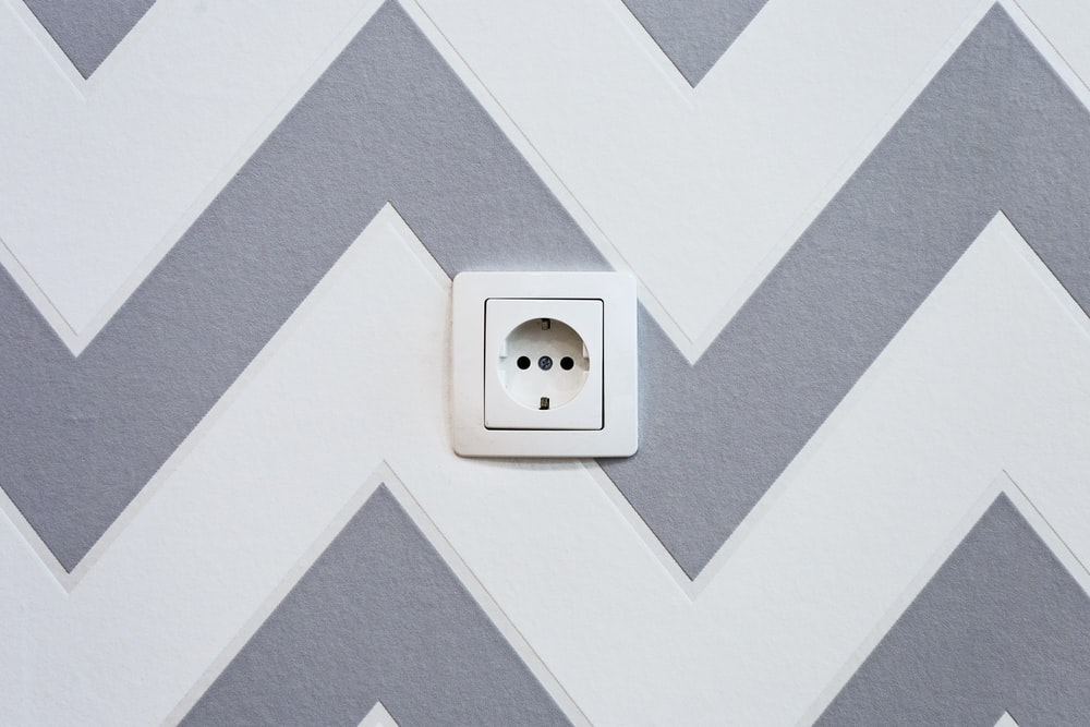 white power strip mounted on white and grey chevron painted wall