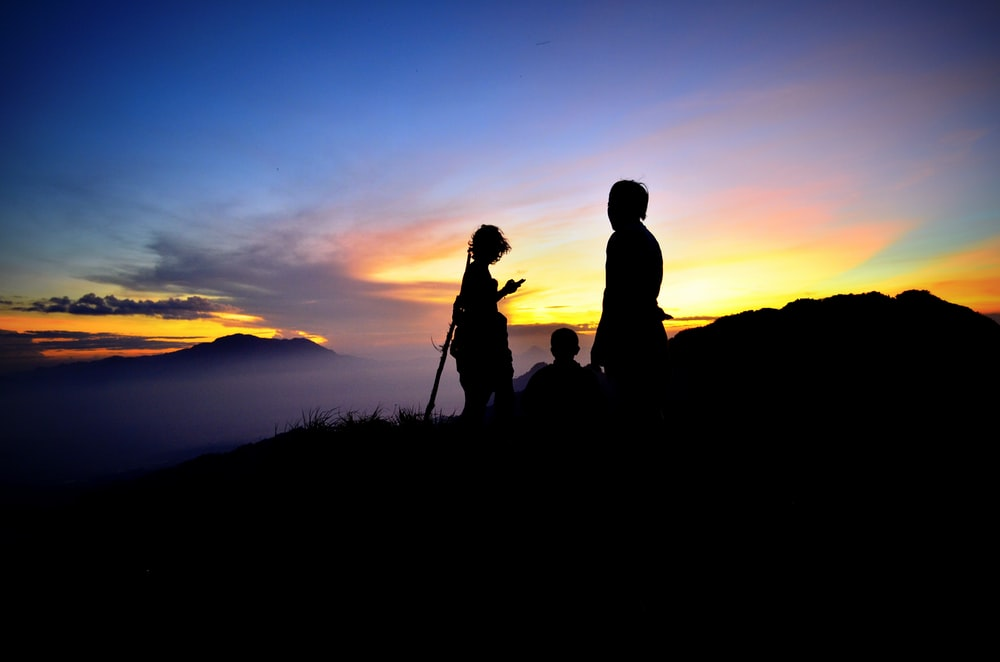 silhouette photography of three persons on mountain during golden hour