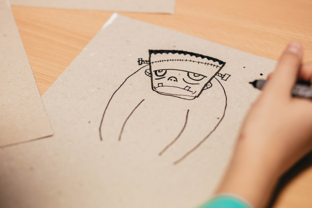 person drawing Frankenstein on brown board