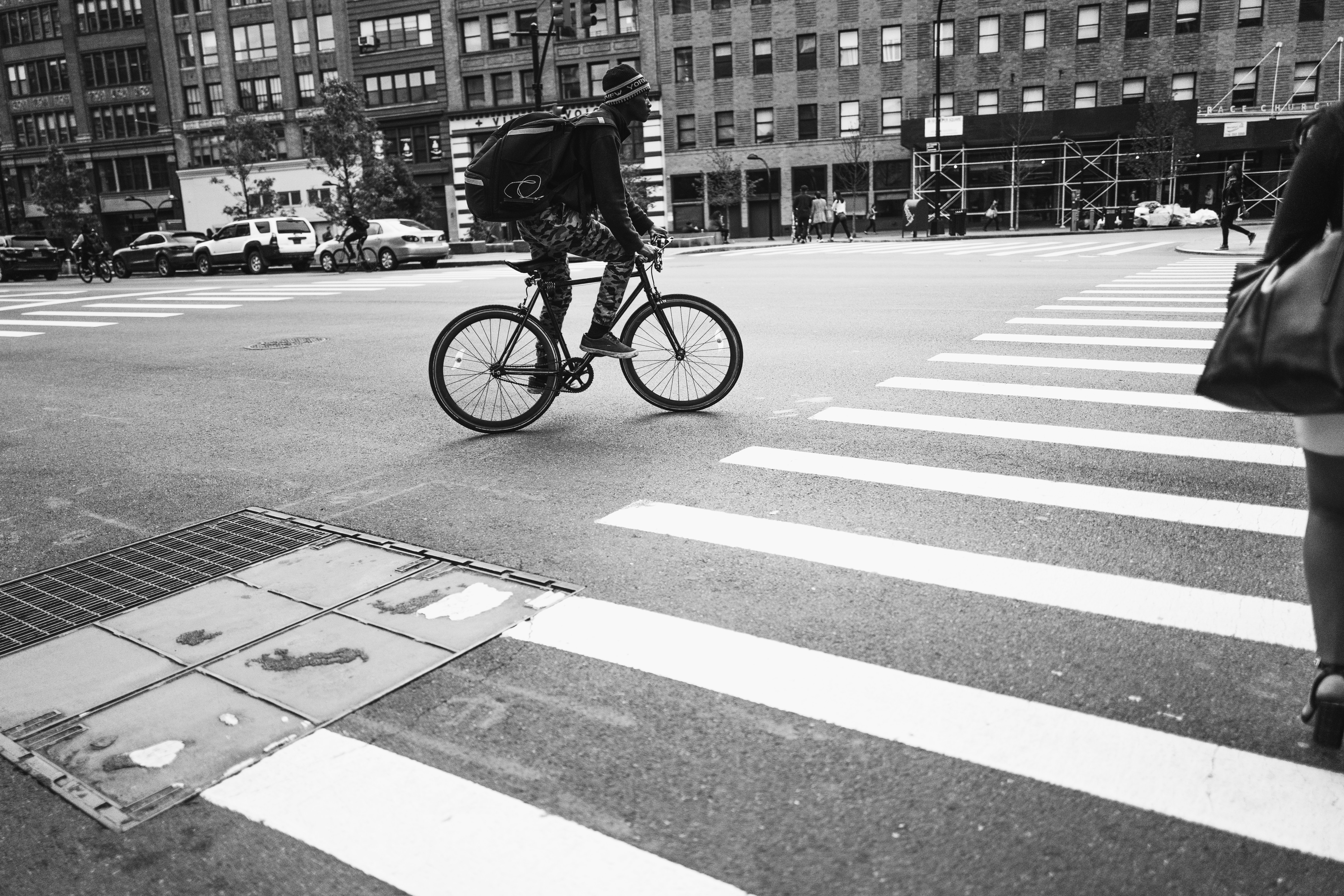 grayscale photography of man riding bicycle crossing pedestrian lane