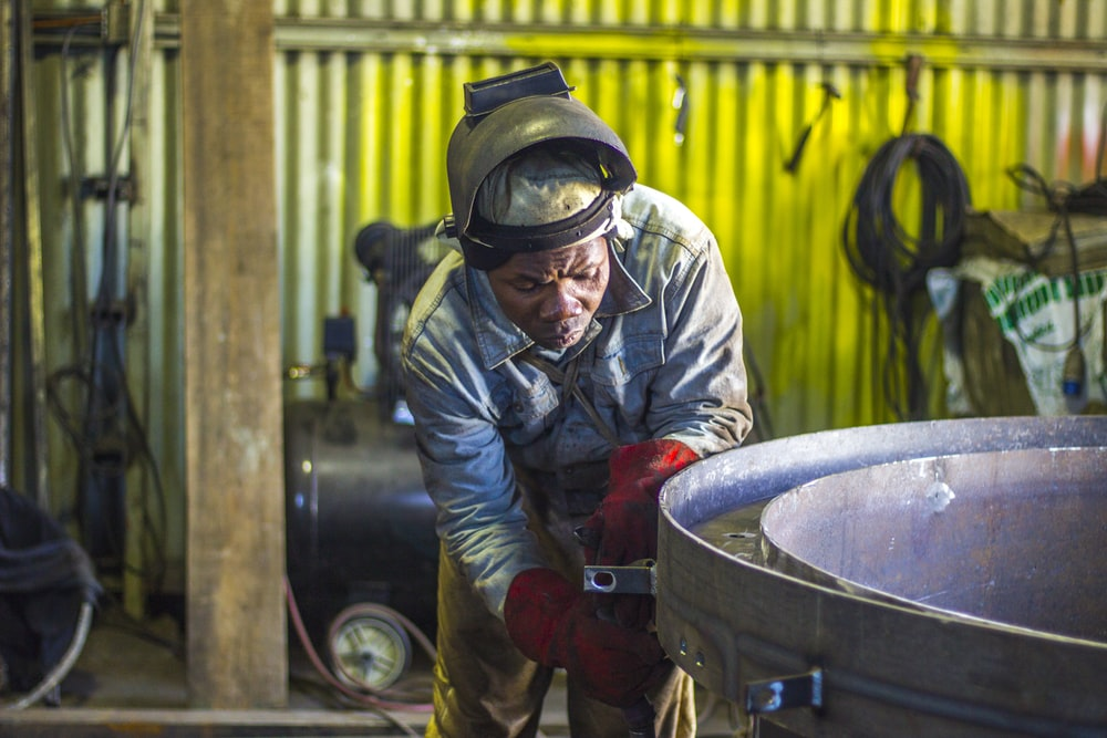 man welding a gray metal container