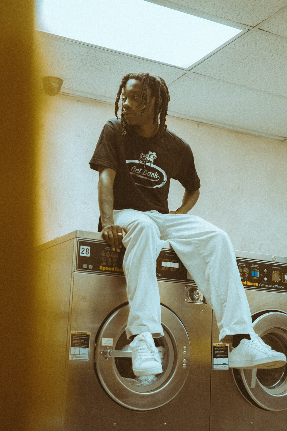 man sitting on top of front-load clothes washer