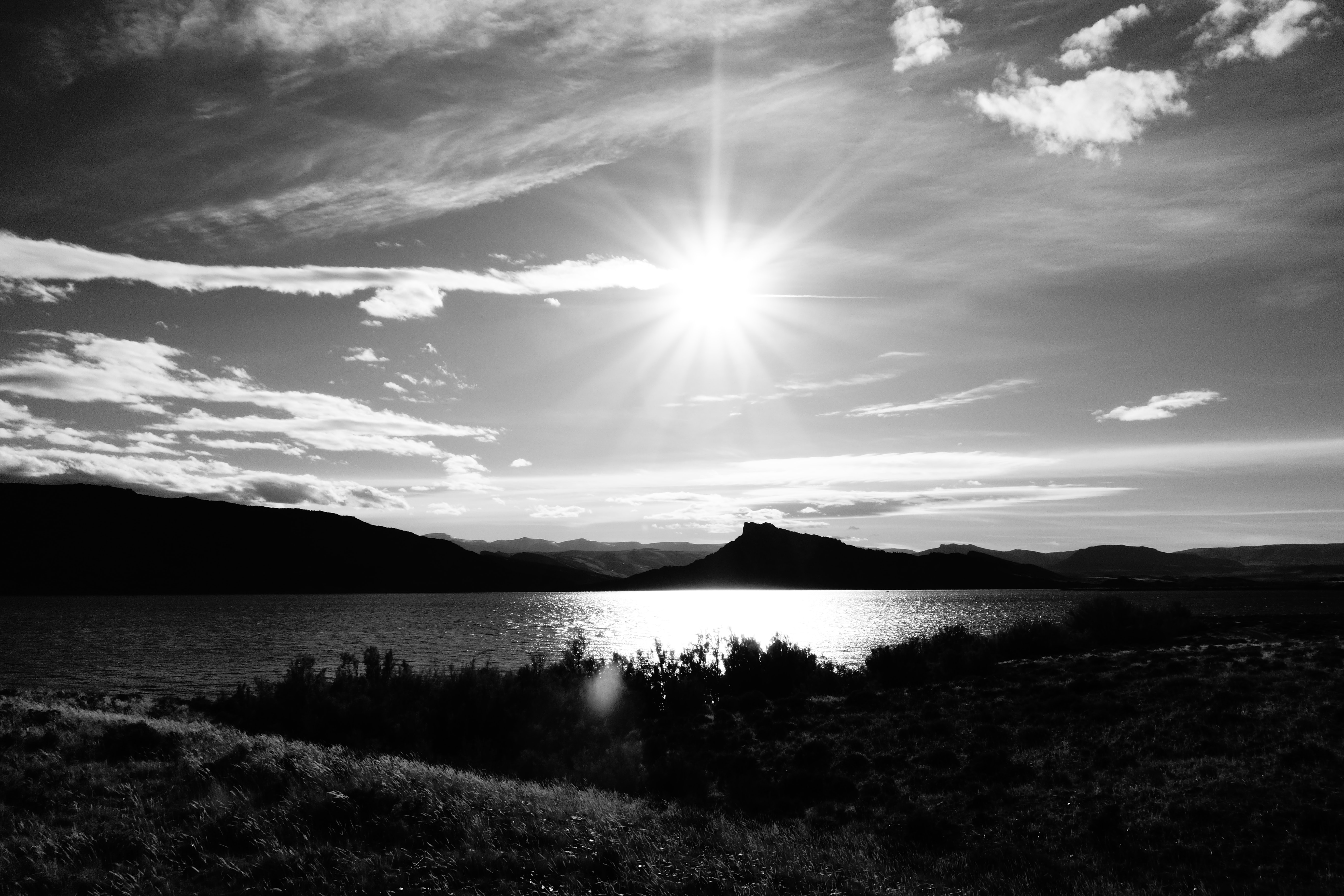 grayscale photography of body of water near mountain