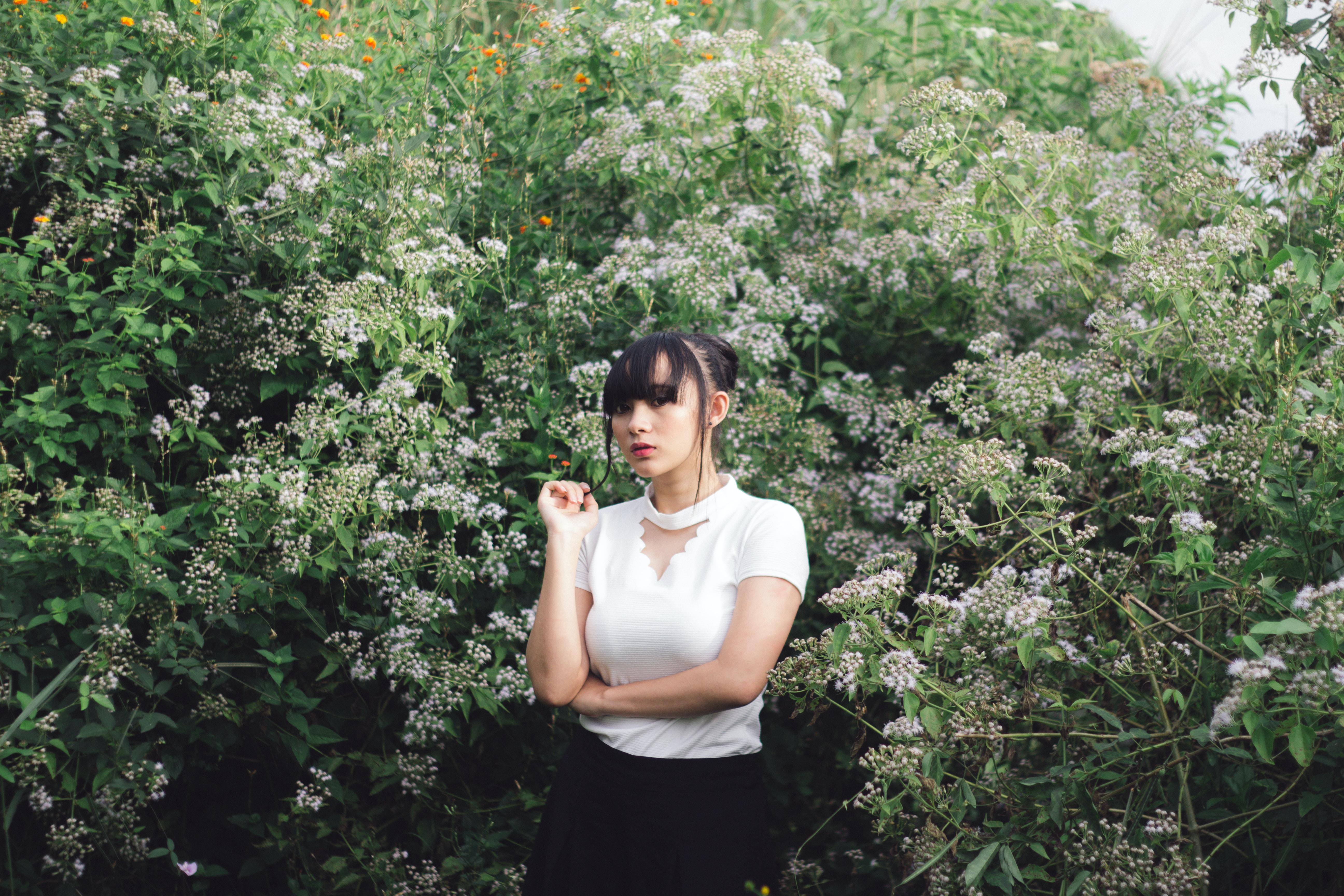 woman standing beside white petaled flower