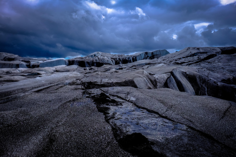 brown rock formation under black sky during daytime