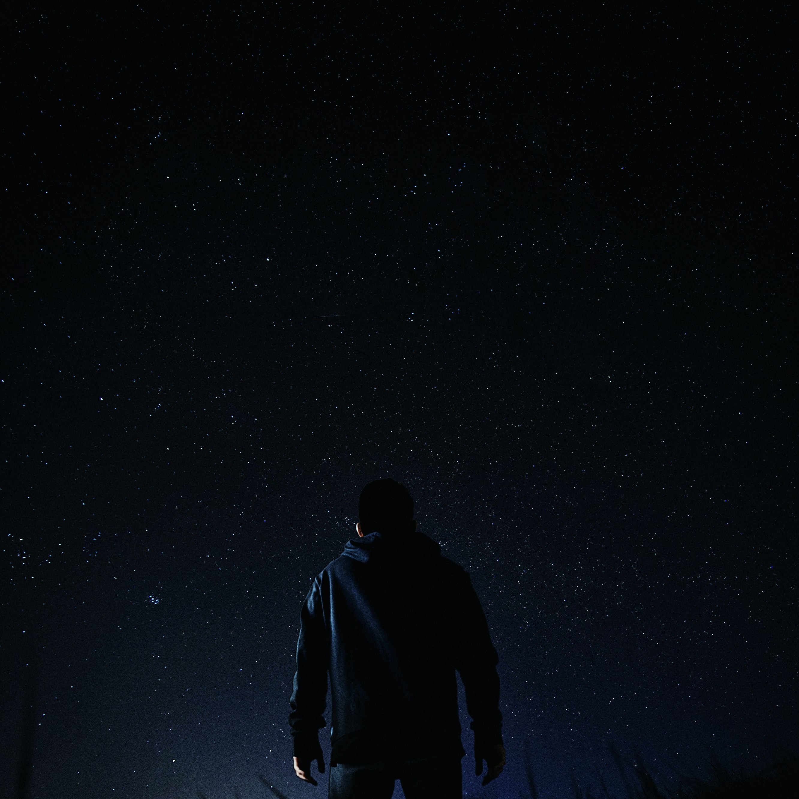 man standing under milky way