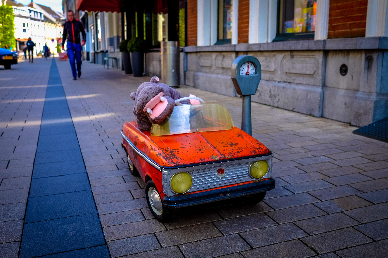 hippopotamus mascot riding red car toy beside the street