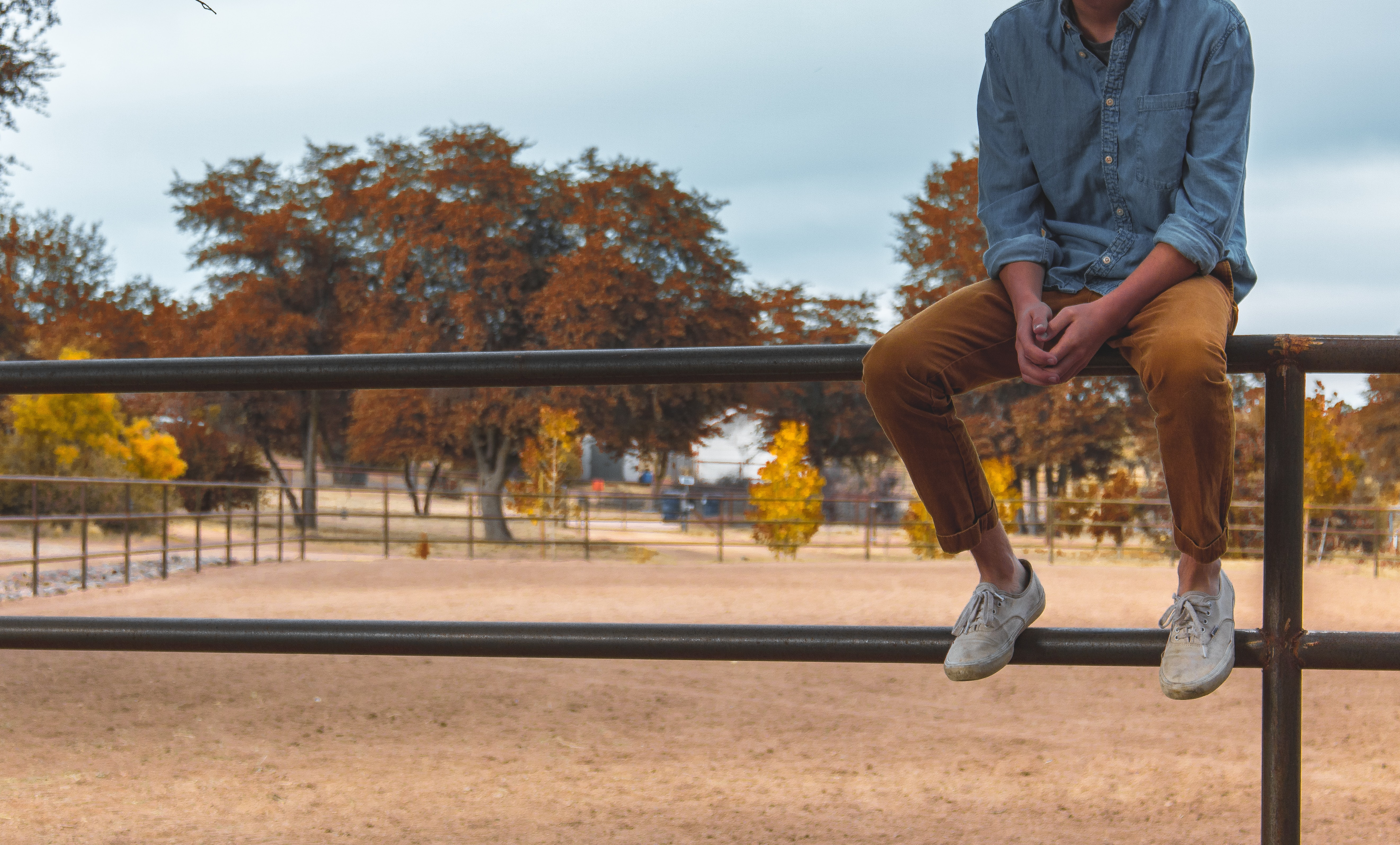 shallow focus photography of person sitting on rail way