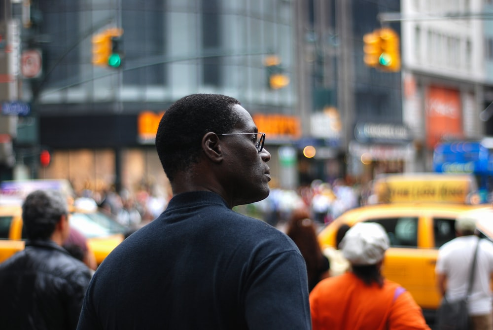 selective focus photography of man standing near road and buildings surrounded with crowd