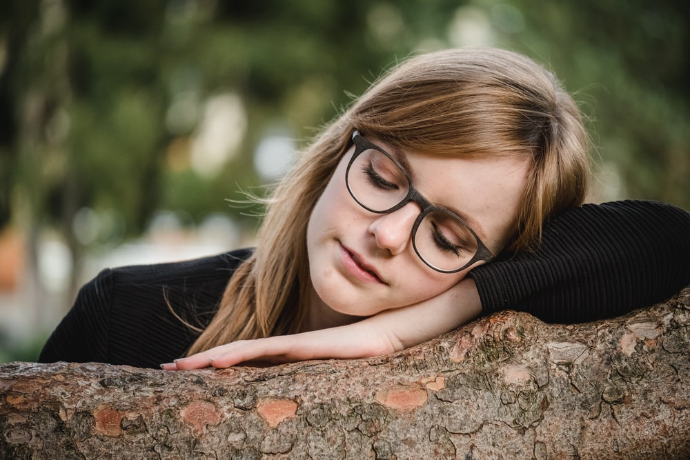 tilt shift photography of woman sleeping on log