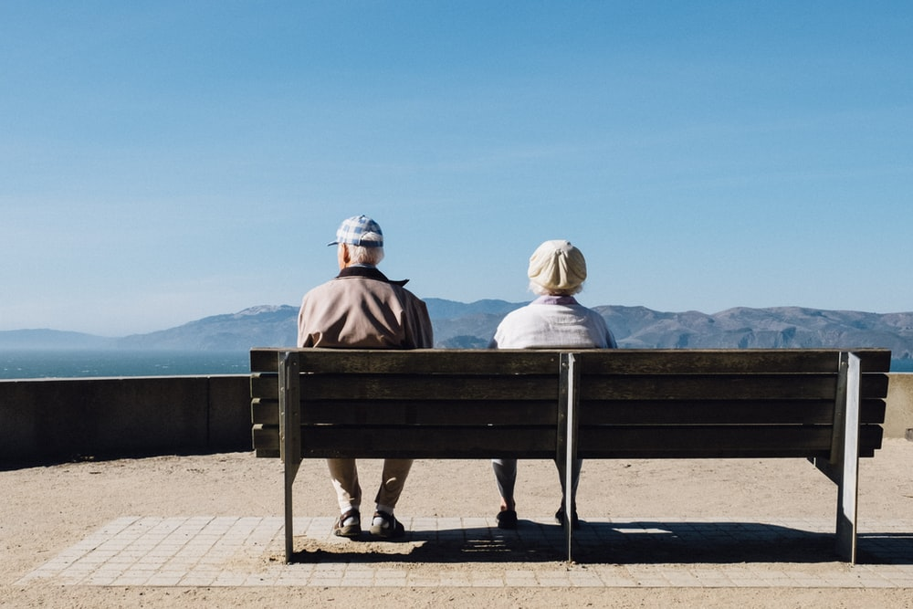 man and woman sitting on bench facing sea
