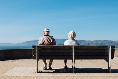 man and woman sitting on bench facing sea old teams background
