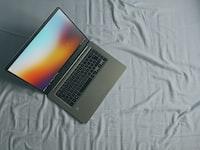 gray Asus laptop on white bed sheet