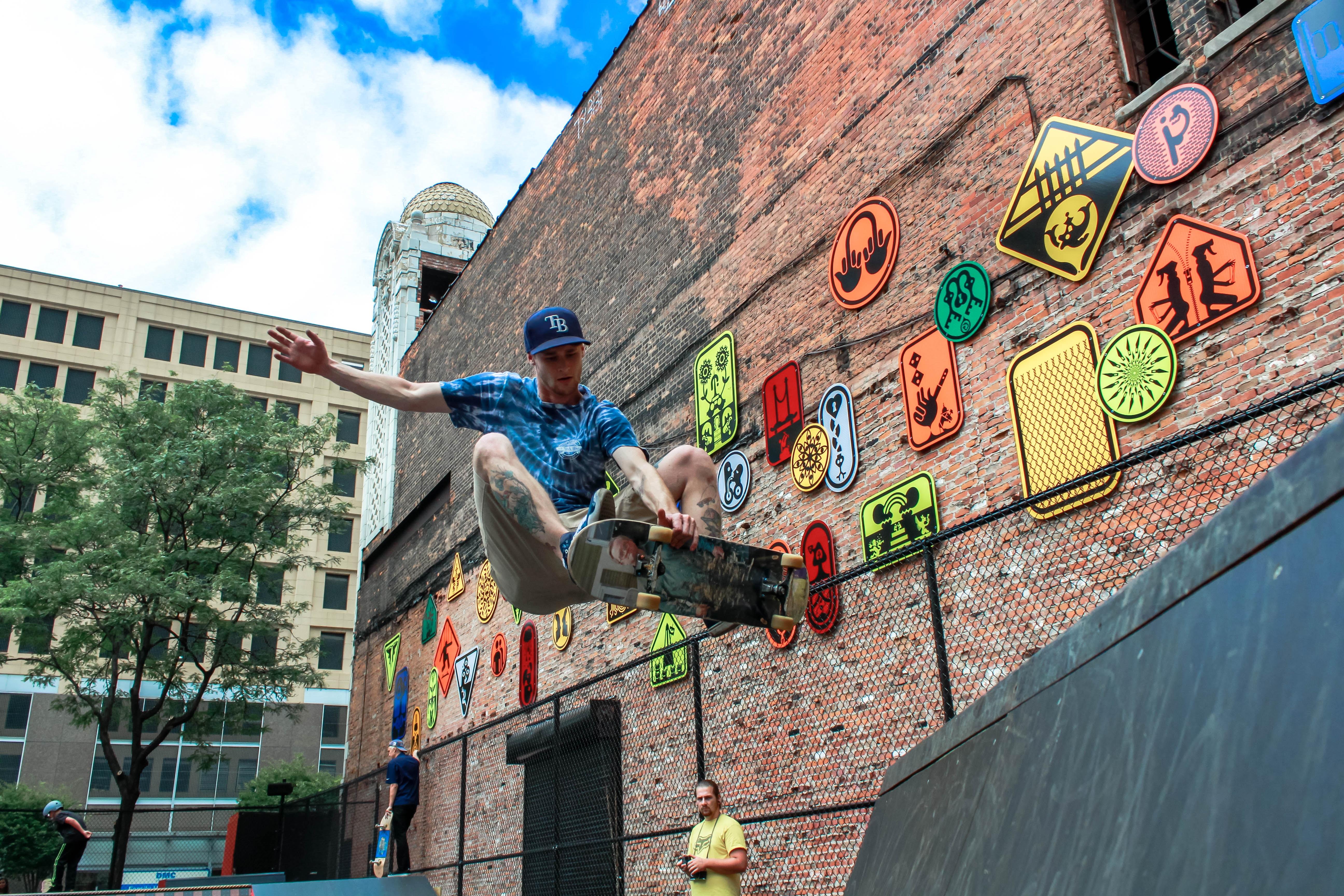 man skateboarding near brown concrete building during daytime