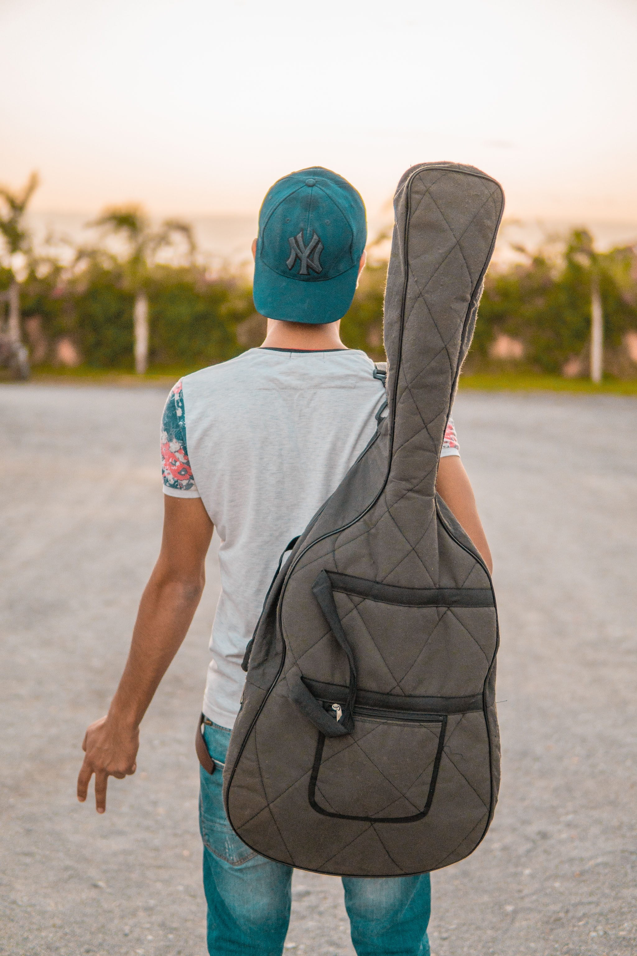 man looking at green trees carrying grey guitar case