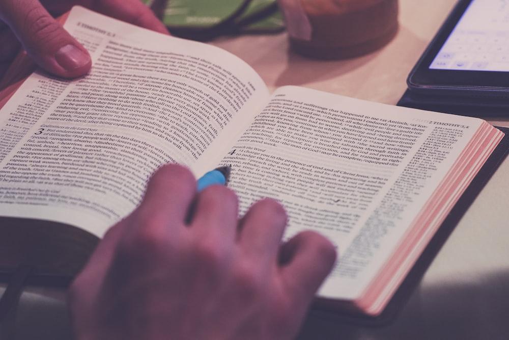 person holding blue pen