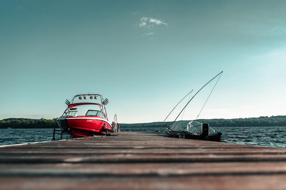 speedboat beside dock under clear sky