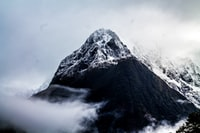 gray and black mountain surrounded by fog under white sky during daytime
